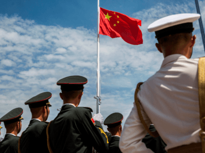 Soldiers of the Peoples' Liberation Army (PLA) during a flag raising ceremony at an open day at the Ngong Shuen Chau Barracks in Hong Kong on June 30, 2019, to mark the 22nd anniversary of Hong Kong's handover from Britain to China on July 1. (Photo by ISAAC LAWRENCE / …