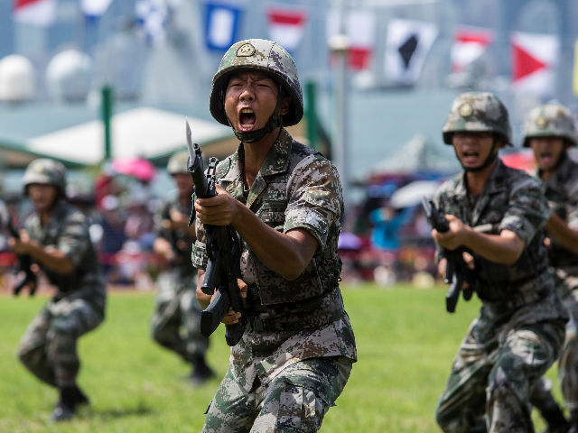 Soldiers of the Peoples' Liberation Army (PLA) perform drills during a demonstration at an open day at the Ngong Shuen Chau Barracks in Hong Kong on June 30, 2019, to mark the 22nd anniversary of Hong Kong's handover from Britain to China on July 1. (Photo by ISAAC LAWRENCE / …