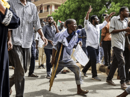 A Sudanese protester walking with a crutch joins others in a march during a mass demonstration against the country's ruling generals in the capital Khartoum's twin city of Omdurman on June 30, 2019. (Photo by Ahmed MUSTAFA / AFP) (Photo credit should read AHMED MUSTAFA/AFP/Getty Images)