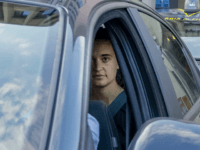 TOPSHOT - German captain of humanitarian ship Sea-Watch 3, Carola Rackete (Rear in car) looks on as she leaves in a car of the Italian Guardia di Finanza law enforcement agency on July 1, 2019 after appearing before a judge at the courthouse in Agrigento, Sicily. - The captain of …