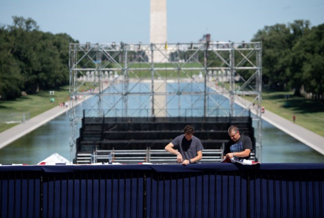 "Workers hang patriotic bunting as they build a stage and bleachers for the ""Salute to America"" Fourth of July event with US President Donald Trump at the Lincoln Memorial on the National Mall in Washington, DC, July 1, 2019, which will feature flyovers by the Blue Angels, an airplane used …"
