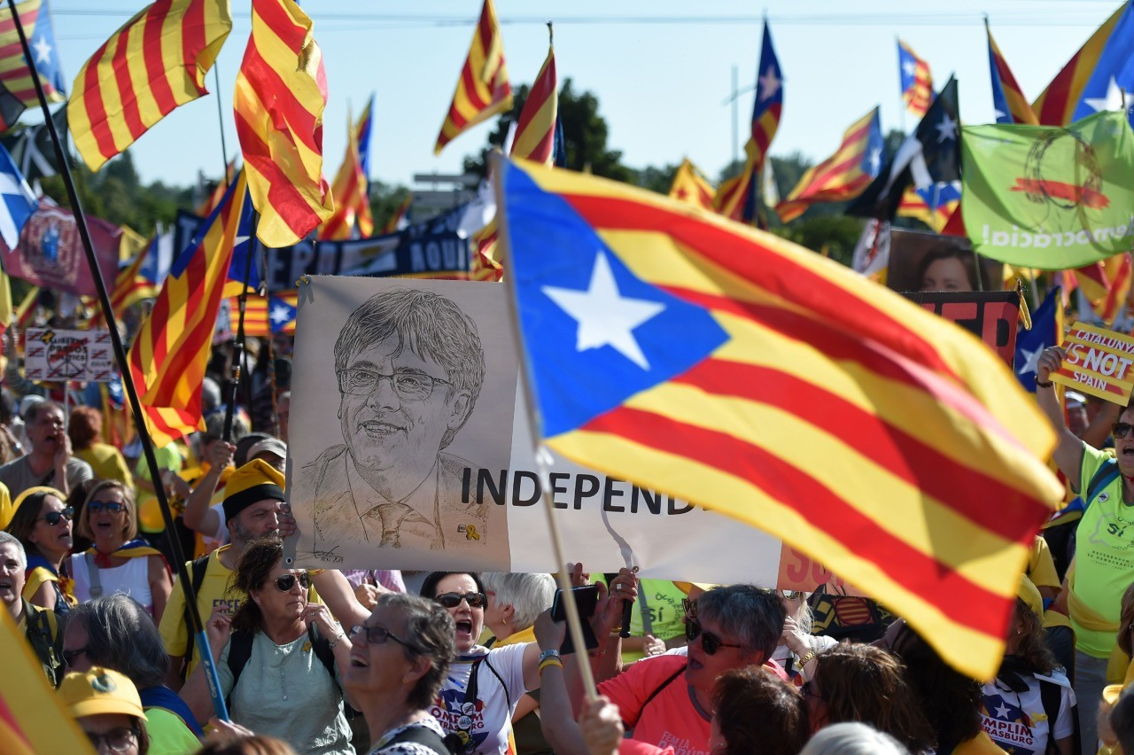 People hold a portrait of ousted Catalan regional president Carles Puigdemont (C) while waving Catalan pro-independence 'Estelada' flags and banners during a demonstration at the European Parliament on July 2 , 2019 in Strasbourg, eastern France. - Demonstrators protest in support of Catalan separatists unable to take seats as MEPs. (Photo by FREDERICK FLORIN / AFP) (Photo credit should read FREDERICK FLORIN/AFP/Getty Images)