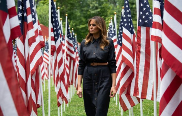 US First Lady Melania Trump walks through 453 American flags, each representing a child in foster care in Cabell County, West Virginia, many due to the opioid epidemic, at Ritter Park in Huntington, West Virginia, July 8, 2019. (Photo by SAUL LOEB / AFP) (Photo credit should read SAUL LOEB/AFP/Getty …