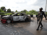 A policeman walks past a car burnt by supporters of an imprisoned leader of the Islamic Movement of Nigeria (IMN) Ibrahim Zakzaky around the national assembly building in Nigeria's capital Abuja, on July 9, 2019. - Supporters of an imprisoned Shiite cleric clashed on July 8, 2019 with security forces …
