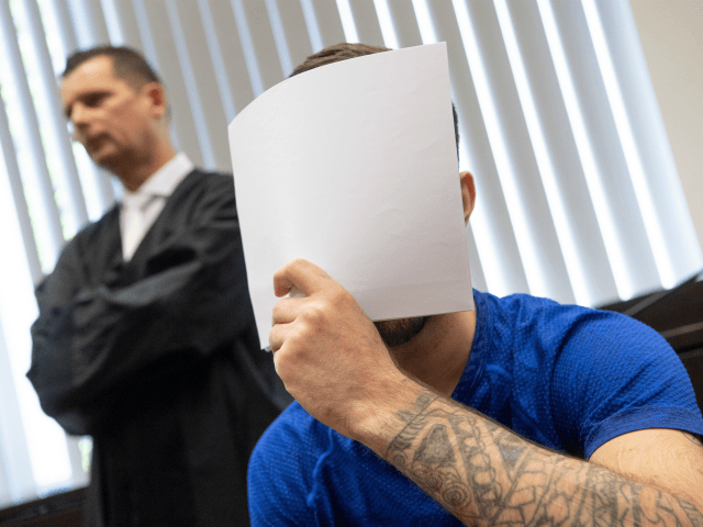 Ali Bashar (R) covers his face in front of the cameras upon entering the courtroom, as his lawyer Martin Reineke looks on, on July 10, 2019 in Wiesbaden, western Germany. - An Iraqi man was sentenced to life in jail by a German court on Wednesday over the rape and …