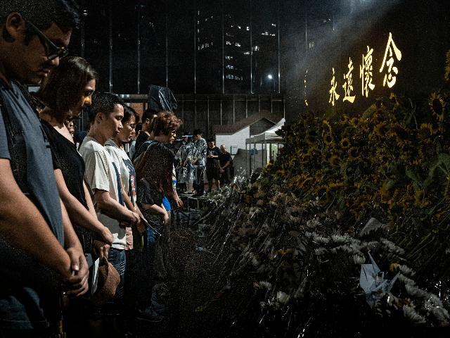 People take a moment of silence during a memorial service on July 11, 2019 in Hong Kong, China. A memorial service was held by public for a man who plunged to death while protesting against the controversial extradition bill. (Photo by Anthony Kwan/Getty Images)