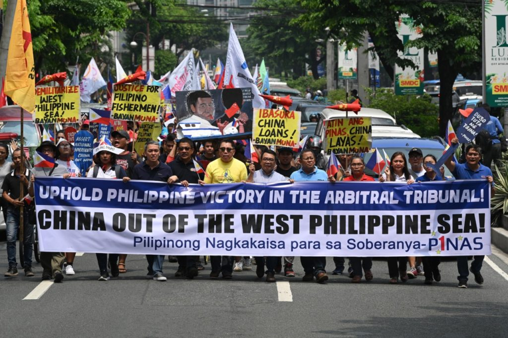 Protesters holding a streamer march towards the Chinese consulate for a rally in Manila on July 13, 2019, to coincide with anniversarry of arbitral ruling by United nations on the South China sea. - Protesters decended on the Chinese consulate in Manila, to oppose the Asian superpower's growing sway in the Philippines and as tensions rise over Beijing's presence in the disputed South China sea. (Photo by Ted ALJIBE / AFP) (Photo credit should read TED ALJIBE/AFP/Getty Images)