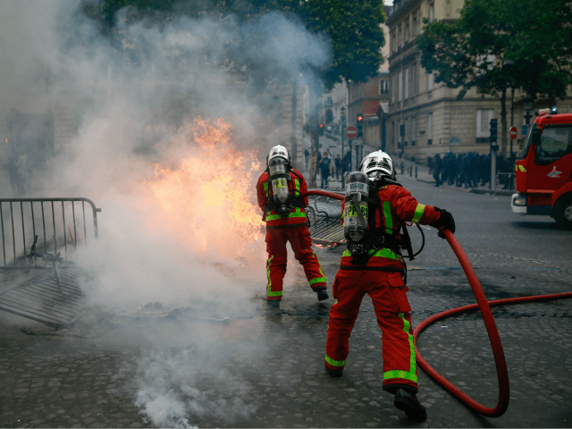 TOPSHOT - Firefighters extinguish a fire as protestors linked to the Yellow Vests (Gilets Jaunes) movement (unseen) take part in a demonstration on the side of the annual Bastille Day ceremony, on July 14, 2019, on the Champs-Elysees in Paris. (Photo by Abdulmonam EASSA / AFP) (Photo credit should read …