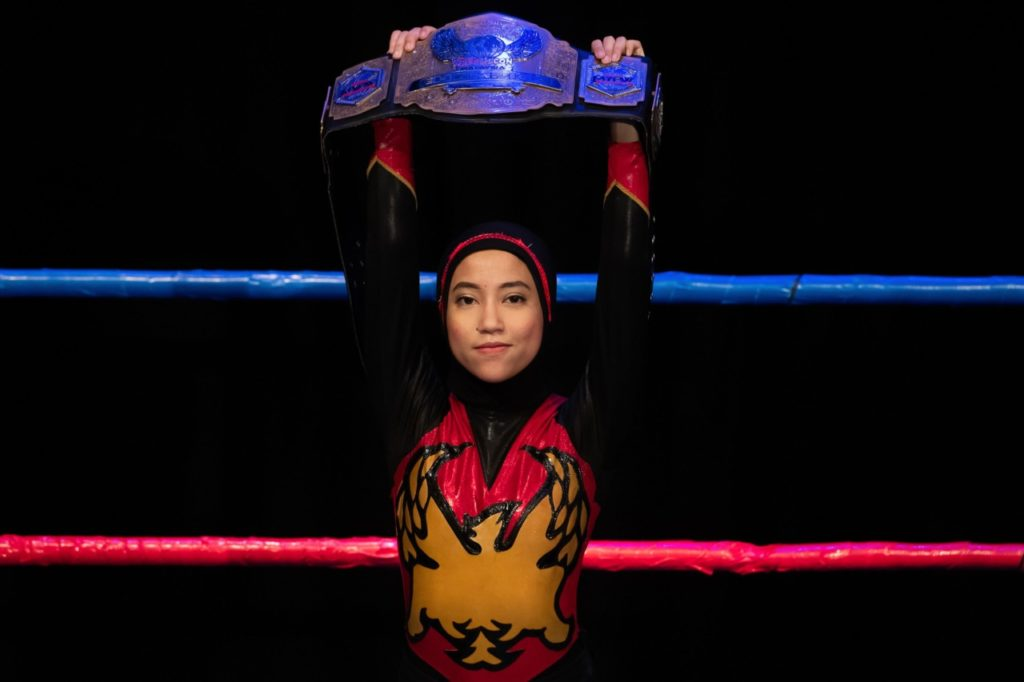 """This picture taken on July 6, 2019 shows the hijab-wearing Malaysian wrestler known as Nor """"Phoenix"""" Diana holding the Wrestlecon championship belt after winning a match against male opponents organised by Malaysia Pro Wrestling in Kuala Lumpur. - A hijab-wearing, diminutive Malaysian wrestler known as """"Phoenix"""" cuts an unusual figure in the ring, a female Muslim fighter taking on hulking opponents in a male-dominated world. (Photo by Mohd RASFAN / AFP) / TO GO WITH Malaysia-wrestling-religion-Islam, FEATURE by Patrick LEE (Photo credit should read MOHD RASFAN/AFP/Getty Images)"""