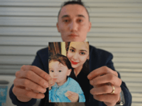 Sadam Abdusalam holds up a photo of his Uighur wife Nadila Wumaier and their baby son Lutifeier at a restaurent in Sydney's western suburbs on July 17, 2019. - Australia's government on July 17 called on China to allow an Australian child and his Uighur mother to leave the country, …