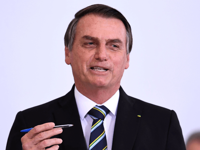 Brazilian President Jair Bolsonaro gestures during a ceremony to commemorate the first 200 days of his administration at Planalto Palace in Brasilia, on July 18, 2019. - Bolsonaro signed a membership application for the Organisation for Economic Co-operation and Development (OECD) during the ceremony. (Photo by EVARISTO SA / AFP) …