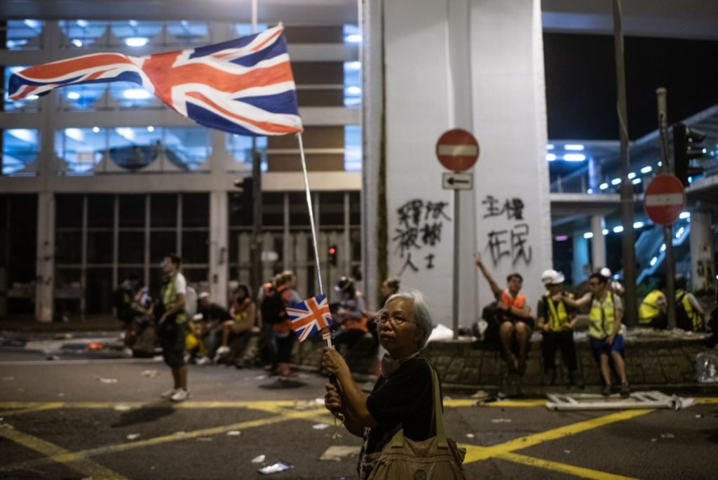 A woman waves UK flags after clashes between protesters and police following a march against a controversial extradition bill in Hong Kong early on July 22, 2019. - Masked protesters daubed the walls of China's office in Hong Kong with eggs and graffiti July 21 night following another massive rally, focusing anger towards the embodiment of Beijing's rule with no end in sight to the turmoil engulfing the finance hub. (Photo by Philip FONG / AFP) (Photo credit should read PHILIP FONG/AFP/Getty Images)