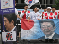 South Korean protestors hold a banner showing a picture of Japanese Prime Minister Shinzo Abe during a rally denouncing Japan for its recent trade restrictions against Seoul over wartime slavery disputes, near the Japanese embassy in Seoul on July 23, 2019. - After South Korea's high court ordered Japanese firms …