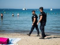 "French gendarmes patrol on the beach near the ""Fort de Bregancon"", in Bormes-les-Mimosas, southern France, where the French President is staying during his summer holidays in the Fort de Bregancon, on July 26, 2019. (Photo by CLEMENT MAHOUDEAU / AFP) (Photo credit should read CLEMENT MAHOUDEAU/AFP/Getty Images)"