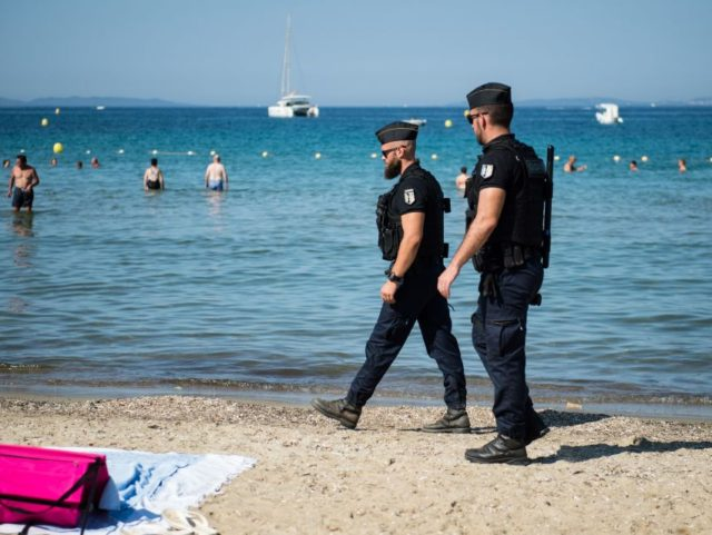 """French gendarmes patrol on the beach near the """"Fort de Bregancon"""", in Bormes-les-Mimosas, southern France, where the French President is staying during his summer holidays in the Fort de Bregancon, on July 26, 2019. (Photo by CLEMENT MAHOUDEAU / AFP) (Photo credit should read CLEMENT MAHOUDEAU/AFP/Getty Images)"""
