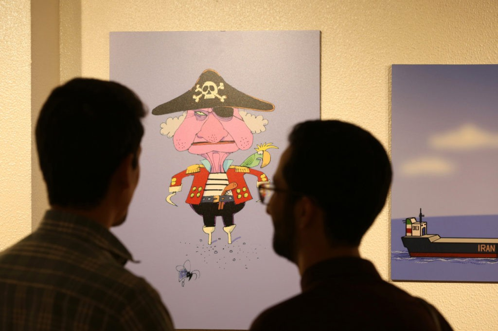 """People view caricatures at the """"Pirates of the Queen"""" cartoon exhibition showing artwork by Iranian artists portraying Britain's Queen Elizabeth II as a """"pirate"""" over the seizure of an Iranian oil tanker earlier in the month, at the Osveh Art and Cultural Center in the capital Tehran on July 30, 2019. - Historically strained ties between Tehran and London worsened when British Royal Marines took part in the seizure of Iran's """"Grace 1"""" oil tanker off UK overseas territory Gibraltar on July 4. That was followed by the seizure by Iran's Islamic Revolutionary Guard Corps of a UK-flagged tanker in the Strait of Hormuz on July 19 -- in what Britain called a """"tit-for-tat"""" move. Forty cartoons have gone on display to throw the spotlight on the British seizure, which saw supreme leader Ayatollah Ali Khamenei accuse the """"vicious British"""" of """"piracy"""". (Photo by ATTA KENARE / AFP) (Photo credit should read ATTA KENARE/AFP/Getty Images)"""