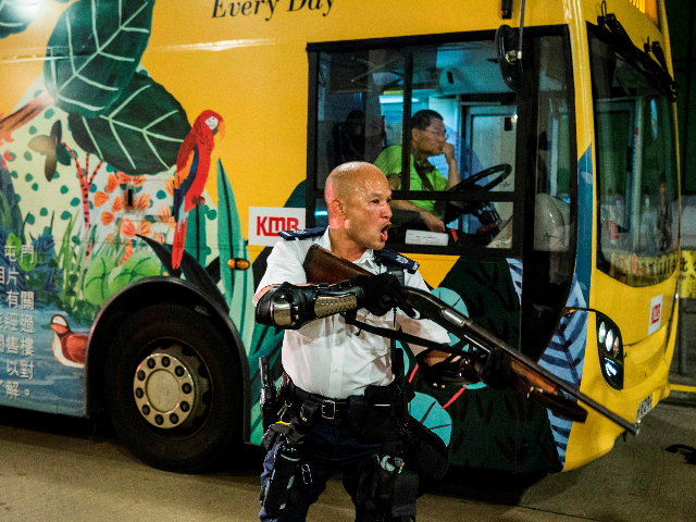 A police officer holds a firearm during clashes with protesters who had gathered outside Kwai Chung police station, in support of protesters detained with the charge of rioting, in Hong Kong on July 30, 2019. (Photo by ISAAC LAWRENCE / AFP) (Photo credit should read ISAAC LAWRENCE/AFP/Getty Images)