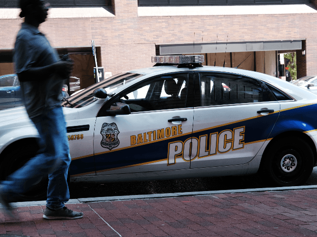 """A person walks past a police car on July 28, 2019 in Baltimore, Maryland. President Donald Trump has recently drawn criticism by calling the city of Baltimore """"disgusting."""" While the struggling city has a number of affluent areas, it has a stubborn crime problem and has one of the highest …"""