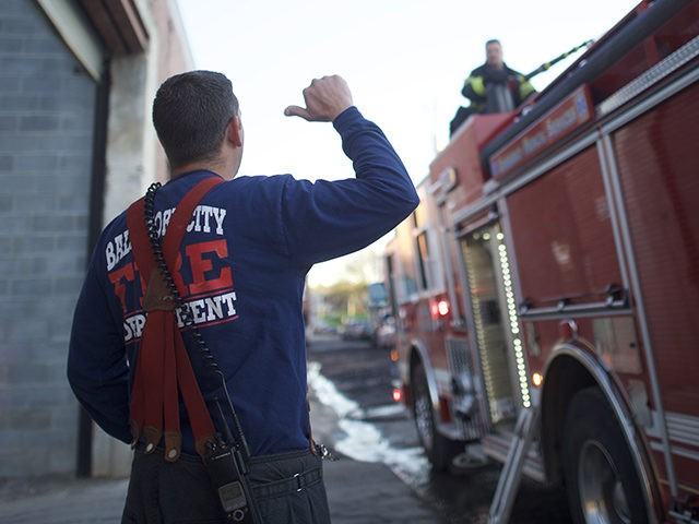 BALTIMORE, MD - APRIL 28: A firefighter motions to a fireman spraying water from a firetruck to extinguish the smoldering remains of a senior center set ablaze during night riots on April 28, 2015 in Baltimore, Maryland. A state of emergency has been declared in Baltimore following violent protests which …