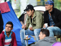 """Men smoke from a waterpipe at a makeshift tent camp in a park in Brussels on September 9, 2015, as they wait to have their asylum claims processed. The camp is situated across the """"Office des Etrangers"""" (Foreigner's Office), where the number of refugees encamped has passed the 250 inscriptions …"""