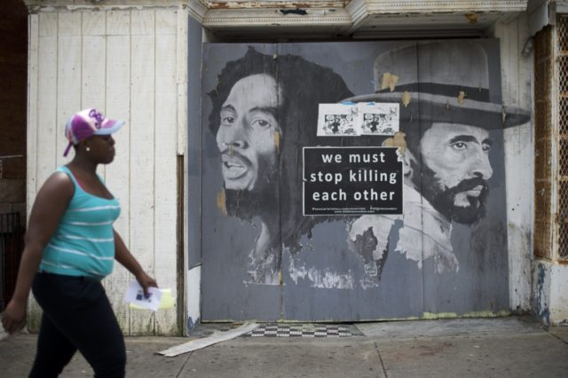 """BALTIMORE, MD - JUNE 23: A woman walks past a """"We Must Stop Killing Each Other"""" sign after Baltimore police officer Caesar Goodson Jr. was found not guilty on all charges on June 23, 2016 in Baltimore, Maryland. Officer Goodson, the van driver in the Freddie Gray case, is facing …"""