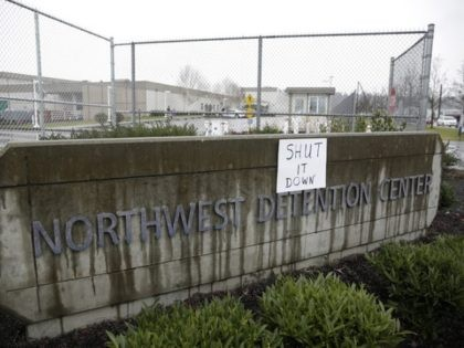 """A sign that reads """"shut it down"""" is pictured at the Northwest Detention Center as people attend the Peoples Tribunal Against the Detention Center event in Tacoma, Washington on February 26, 2017. / AFP / Jason Redmond (Photo credit: JASON REDMOND/AFP/Getty Images)"""