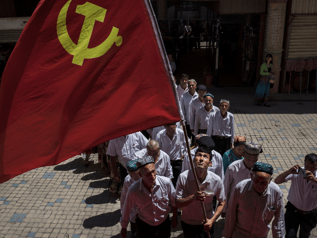 thnic Uyghur members of the Communist Party of China carry a flag as they take part in an organized tour on June 30, 2017 in the old town of Kashgar, in the far western Xinjiang province, China. Kashgar has long been considered the cultural heart of Xinjiang for the province's …