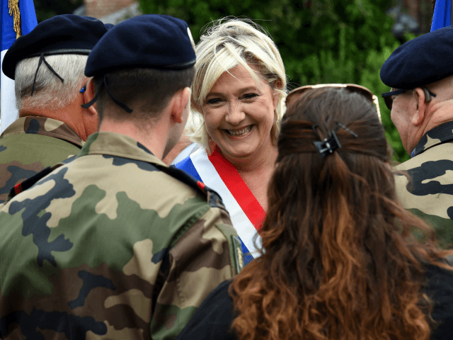 Far-right Front National (FN) party member of parliament Marine Le Pen speaks with military personnel as she attend the annual Bastille Day celebrations in Henin-Beaumont, northwestern France on July 14, 2017. / AFP PHOTO / FRANCOIS LO PRESTI (Photo credit should read FRANCOIS LO PRESTI/AFP/Getty Images)