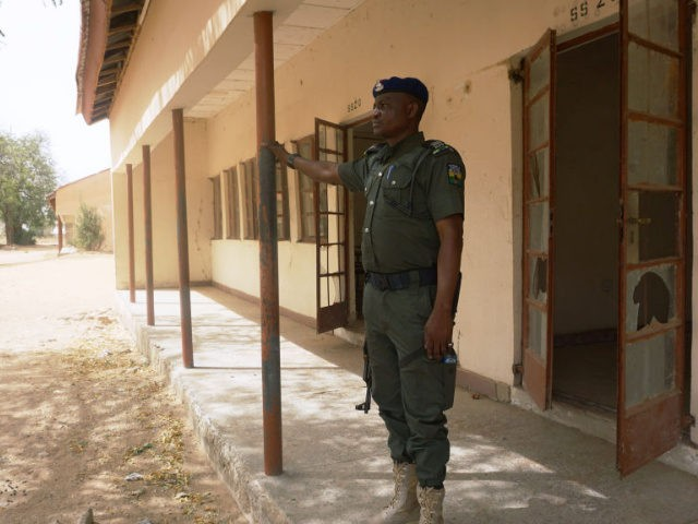 A policeman stands on guard at the premises of Government Girls Technical College, where 110 girls were kidnapped by Boko Haram Islamists at Dapchi town in northern Nigerian on February 28, 2018.
