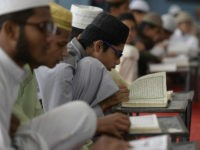 Indian Muslim students recite from the Quran in a classroom during the holy month of Ramadan at Al Mahad Al Dini Al Arabi in Hyderabad on May 24, 2018. - As well as abstinence and fasting during Ramadan, Muslims are encouraged to pray and read the Quran during Islam's holiest …