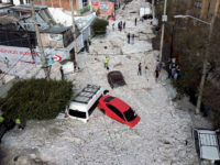 TOPSHOT - Vehicles buried in hail are seen in the streets in the eastern area of Guadalajara, Jalisco state, Mexico, on June 30, 2019. - The accumulation of hail in the streets of Guadalajara buried vehicles and damaged homes. (Photo by ULISES RUIZ / AFP) (Photo credit should read ULISES …