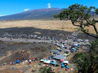 In this Sunday, July 21, 2019, photo provided by the Hawaii Department of Land and Natural Resources, protesters block a road to the summit of Mauna Kea in Hawaii. Scientists want to build the telescope atop Mauna Kea because it is one of the best sites in the world for …