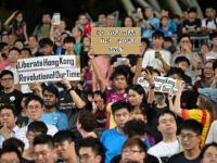 Protesters hold up signs related to the recent political events and demonstrations in the territory, during the first half of the friendly football match between English Premier League club Manchester City and Hong Kong side Kitchee at Hong Kong Stadium on July 24, 2019. (Photo by Anthony WALLACE / AFP) …