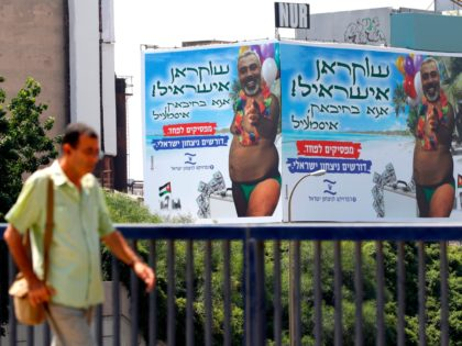 A picture taken on July 23, 2019 in the Israeli coastal city of Tel Aviv, shows a giant billboard bearing the portrait of Hamas leader Ismail Haniyeh super-imposed on a body of a man in a swimsuit and carrying a suitcase of money. - Hebrew writing on the billboard reads: …