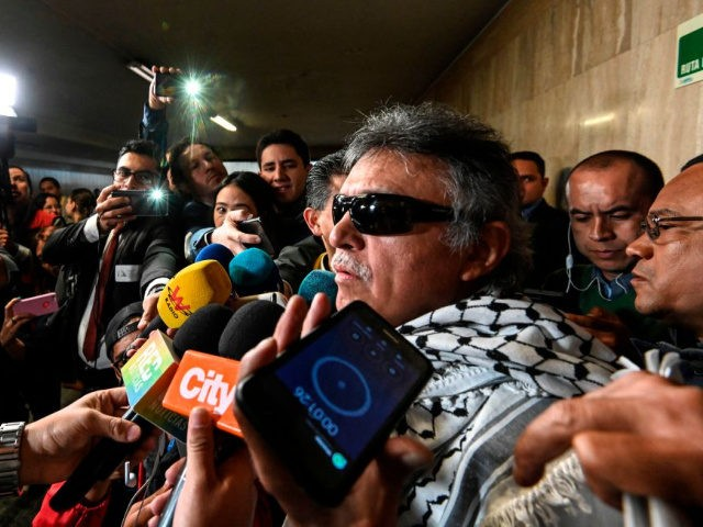 """Common Alternative Revolutionary Force (FARC) party member Jesus Santrich (R), wanted by the United States for drug-trafficking, speaks to the press after swearing in as congressman in Bogota, on June 11, 2019. - Former Marxist rebel leader Santrich, 52, hailed it as """"a new step in the fight and defense …"""