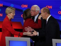 Democratic presidential candidates Sen. Elizabeth Warren (D-MA) (L) greets former Maryland congressman John Delaney (R) while Sen. Bernie Sanders (I-VT) hugs Sen. Amy Klobuchar (D-MN) after the Democratic Presidential Debate at the Fox Theatre July 30, 2019 in Detroit, Michigan. 20 Democratic presidential candidates were split into two groups of …