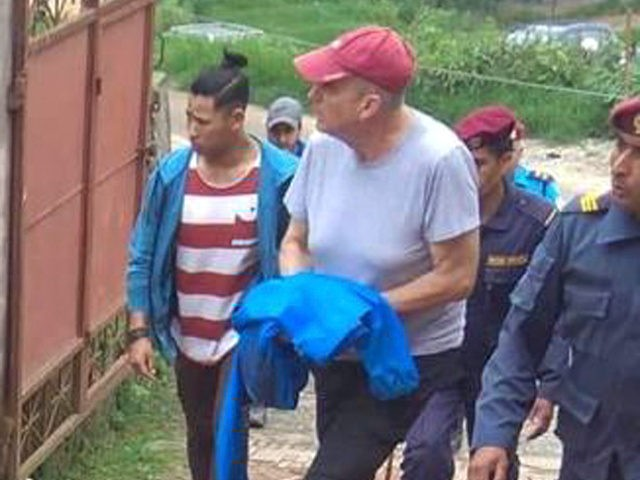 In this Monday, July 8, 2019 photo, Canadian aid worker Peter Dalglish, center wearing red cap, is brought to appear before the Kavre District Court in Nepal. Dalglish was Monday sentenced to nine years in prison in Nepal for sexually abusing two boys who were found at his home. (AP …