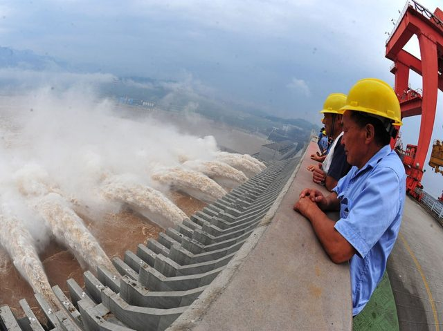This picture taken on July 24, 2012 shows workers watching as water is released from the Three Gorges Dam, a gigantic hydropower project on the Yangtze river, in Yichang, central China's Hubei province, after heavy downpours in the upper reaches of the dam caused the highest flood peak of the …