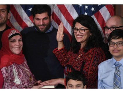 Rep. Rashida Tlaib (center), wearing a traditional Palestinian robe, takes the oath of office on a Quran at the start of the 116th Congress at the U.S. Capitol on Thursday. Saul Loeb/AFP/Getty Images