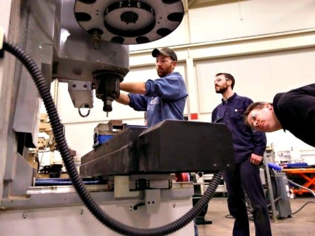 In a photo from Wednesday, Feb. 11, 2015 in Lansing, Mich., Lansing Community College, Brad Bancroft, left, operates a mill as Nate Joseph, center, and Adam Woodhams, right, look on in the advanced precision machining class. (AP Photo/Carlos Osorio)