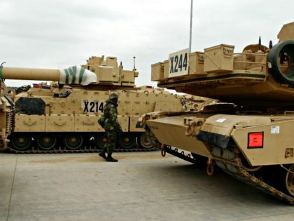 FT. HOOD, TX - JANUARY 22: A soldier walks among military vehicles ready for deployment to the Middle East January 22, 2003 at Ft. Hood, Texas. In addition to M1A2 Abrams tanks, Bradley Fighting Vehicles and other equipment, 12,500 members of the 4th Infantry Division, which is housed at Ft. …
