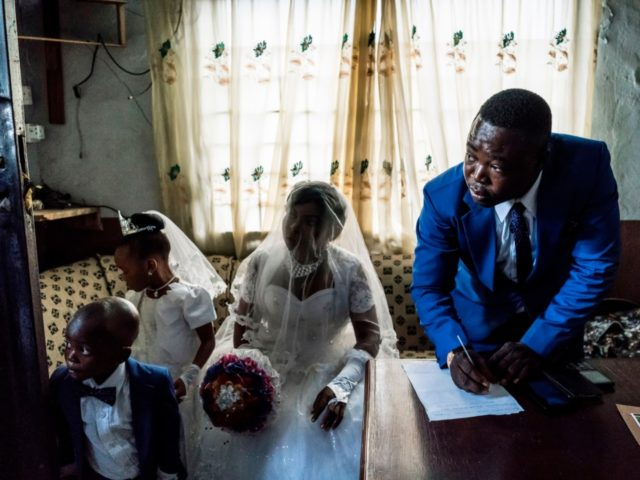 OPSHOT - Chinyere (Godgiven) and her husband-to-be Jones (R) prepare wedding documents during a service at the Evangelic Calvary Life Mission Church on May 28, 2017 in the Osusu district of Aba. / AFP PHOTO / MARCO LONGARI (Photo credit should read MARCO LONGARI/AFP/Getty Images)