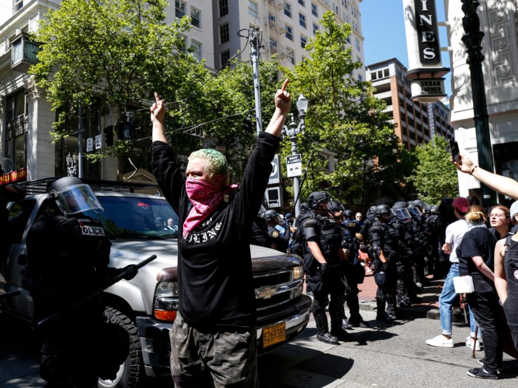 PORTLAND, OR - JUNE 29: An unidentified Rose City Antifa member flicks off to the police during a demonstration between the left and right at Pioneer Courthouse Square on June 29, 2019 in Portland, Oregon. Several groups from the left and right clashed after competing demonstrations at Pioneer Square, Chapman Square, and Waterfront Park spilled into the streets. According to police, medics treated eight people and three people were arrested during the demonstrations. (Photo by Moriah Ratner/Getty Images)