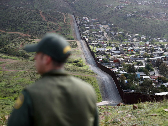 FILE - In this Feb. 5, 2019, file photo, Border Patrol agent Vincent Pirro looks on near a border wall that separates the cities of Tijuana, Mexico, and San Diego, in San Diego. Hundreds of thousands of people have been arriving at the border in recent months, many of them …