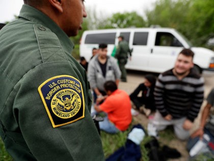 In this Thursday, March 14, 2019, photo, a Border Patrol agent talks with a group suspected of having entered the U.S. illegally near McAllen, Texas. While many adults crossing the border on their own in South Texas try to flee agents, most migrant parents and children wait to surrender so …