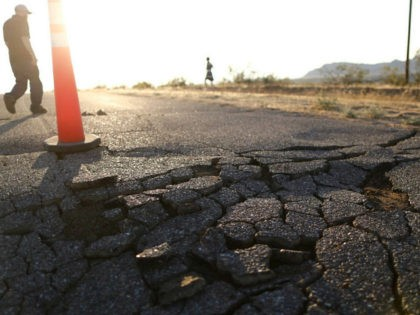 RIDGECREST, CALIFORNIA - JULY 04: People walk near cracks in the road after a 6.4 magnitude earthquake struck the area on July 4, 2019 near Ridgecrest, California. The earthquake was the largest to strike Southern California in 20 years with the epicenter located in a remote area of the Mojave …