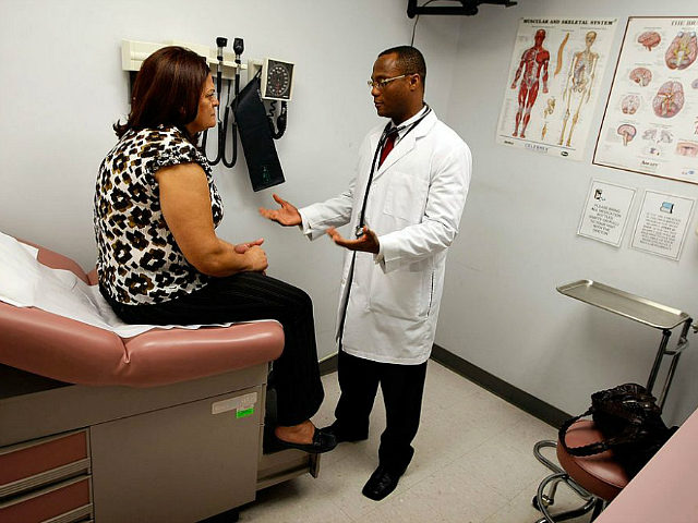 POMPANO BEACH, FL - APRIL 20: Emlyn Louis, MD speaks with Julia Herrera as he examines her at the Broward Community & Family Health Center on April 20, 2009 in Pompano Beach, Florida. Mr. Louis's job was saved when the American Recovery and Reinvestment Act provided funds for community health …