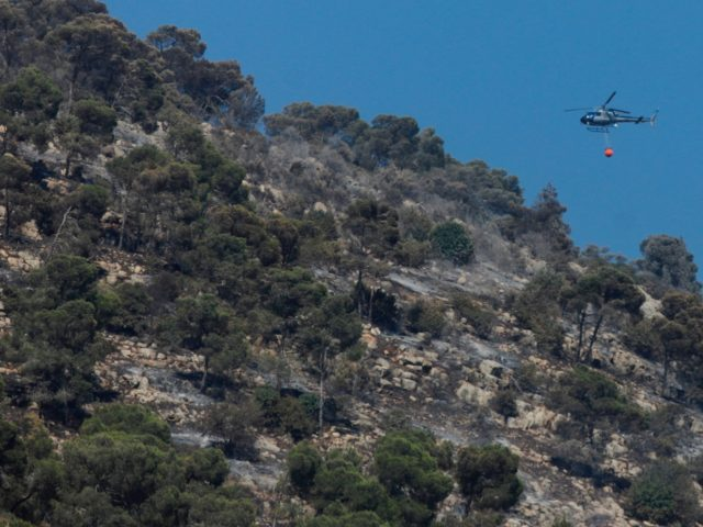 A helicopter tries to extinguish the blaze of a forest fire on Mount Tabor in northern Israel's Galilee region on July 26, 2019. - A forest fire in northern Israel's Galilee region is threatening a church where Christians believe the transfiguration of Jesus took place, the fire service said Friday. …