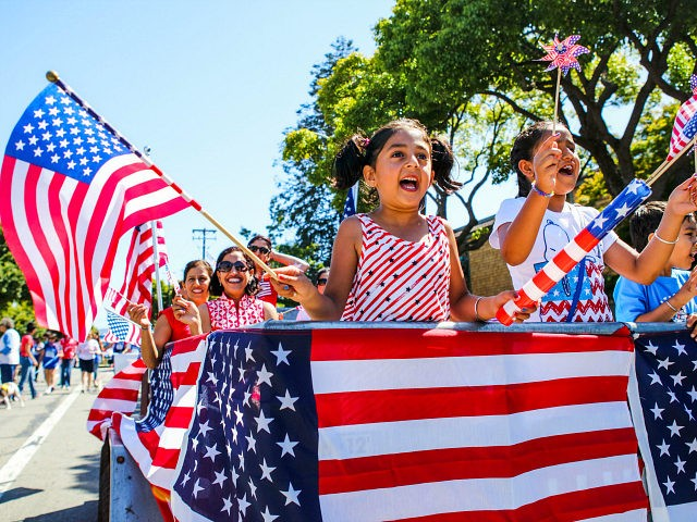 People wave American flags as they ride through 4th of July Parade in Alameda, California on Monday, July 4, 2016. / AFP / GABRIELLE LURIE (Photo credit should read GABRIELLE LURIE/AFP/Getty Images)