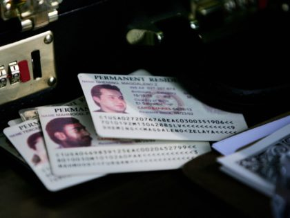 Alexandria, UNITED STATES: Permanent residence cards, known as green cards, rest on the check-in table as resident aliens arrive for a naturalization ceremony at George Washington's Mount Vernon in Alexandria, VA, 22 May 2006. Ninety-five people took the oath of US citizenship at the historic location, home to the first …